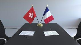 Banderas de Hong Kong y de Francia y papeles en la tabla Negociaciones y firma de un acuerdo internacional Conceptual almacen de video