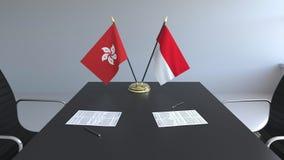 Banderas de Hong Kong y de Indonesia y papeles en la tabla Negociaciones y firma de un acuerdo internacional almacen de video
