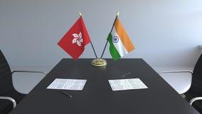 Banderas de Hong Kong y de la India y papeles en la tabla Negociaciones y firma de un acuerdo internacional 3D conceptual almacen de metraje de vídeo
