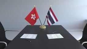 Banderas de Hong Kong y de Tailandia y papeles en la tabla Negociaciones y firma de un acuerdo internacional Conceptual almacen de metraje de vídeo