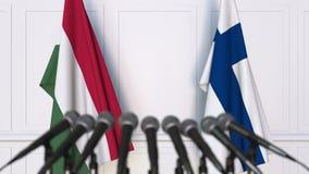 Banderas de Hungría y de Finlandia en la rueda de prensa internacional de la reunión o de las negociaciones animación 3D almacen de metraje de vídeo