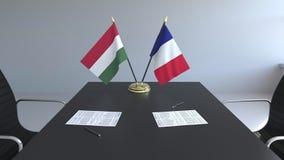 Banderas de Hungría y de Francia y papeles en la tabla Negociaciones y firma de un acuerdo internacional 3D conceptual almacen de metraje de vídeo