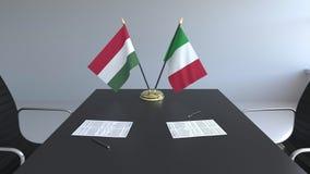 Banderas de Hungría y de Italia y papeles en la tabla Negociaciones y firma de un acuerdo internacional 3D conceptual metrajes