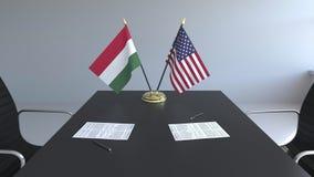Banderas de Hungría y de los Estados Unidos y papeles en la tabla Negociaciones y firma de un acuerdo internacional almacen de metraje de vídeo