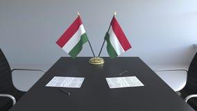 Banderas de Hungría y de papeles en la tabla Negociaciones y firma de un acuerdo Animación conceptual 3D almacen de metraje de vídeo