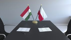 Banderas de Hungría y de Polonia y papeles en la tabla Negociaciones y firma de un acuerdo internacional 3D conceptual metrajes