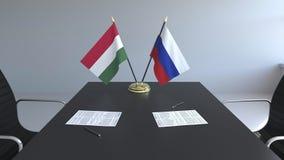 Banderas de Hungría y de Rusia y papeles en la tabla Negociaciones y firma de un acuerdo internacional 3D conceptual metrajes