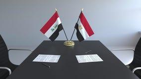 Banderas de Iraq y de Egipto y papeles en la tabla Negociaciones y firma de un acuerdo internacional 3D conceptual almacen de metraje de vídeo