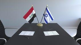 Banderas de Iraq y de Israel y papeles en la tabla Negociaciones y firma de un acuerdo internacional 3D conceptual metrajes
