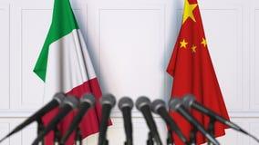 Banderas de Italia y de China en la rueda de prensa internacional de la reunión o de las negociaciones metrajes