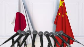 Banderas de Japón y de China en la rueda de prensa internacional de la reunión o de las negociaciones almacen de video