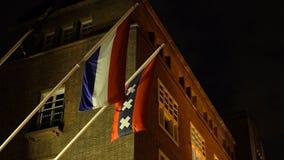 Banderas de la ejecución de Países Bajos y de la ciudad de Amsterdam con tres cruces en la calle de la noche en Holanda después d metrajes
