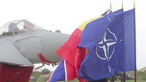 Banderas de la OTAN, de Rumania y de Reino Unido delante de un avión de combate de Royal Air Force Eurofighter Typhoon