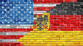 Banderas de la pared de ladrillo los E.E.U.U. y de Alemania Imagen de archivo libre de regalías
