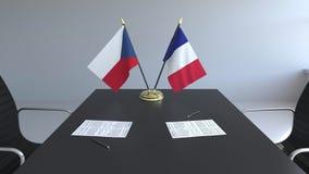 Banderas de la República Checa y de la Francia y papeles en la tabla Negociaciones y firma de un acuerdo internacional metrajes