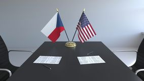 Banderas de la República Checa y de los Estados Unidos y papeles en la tabla Negociaciones y firma de un internacional almacen de metraje de vídeo