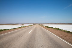 Banderas de la sal del lago seco en el camino del verano con el carril blanco debajo del cielo nublado Imagenes de archivo
