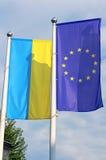 Banderas de la UE y de la Ucrania en la asta de bandera Foto de archivo