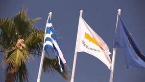 Banderas de la unión europea, Grecia, Chipre, la ciudad de Aya Napa, Grecia, banderas en la asta de bandera, el agitar del viento almacen de metraje de vídeo