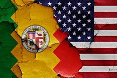 Banderas de Los Ángeles y de los E.E.U.U. pintadas en la pared agrietada Foto de archivo