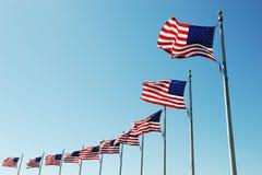 Banderas de los E.E.U.U. en fila contra el cielo azul Foto de archivo libre de regalías