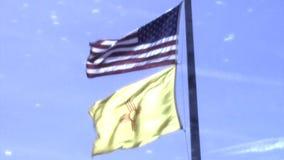 Banderas de los E.E.U.U. y de New México en fuerte viento almacen de metraje de vídeo