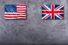 Banderas de los E.E.U.U. y del Reino Unido Bandera de Union Jack en fondo concreto Imagen de archivo