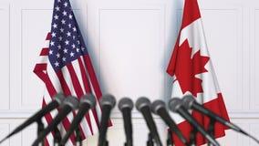 Banderas de los E.E.U.U. y del Canadá en la rueda de prensa internacional de la reunión o de las negociaciones metrajes