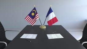Banderas de Malasia y de Francia y papeles en la tabla Negociaciones y firma de un acuerdo internacional 3D conceptual metrajes