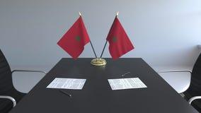 Banderas de Marruecos y de papeles en la tabla Negociaciones y firma de un acuerdo Animación conceptual 3D almacen de metraje de vídeo
