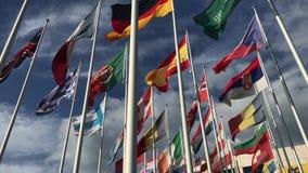 Banderas de muchos países vawing en el viento con el cielo azul y las nubes blancas para el comercio político, internacional, con almacen de metraje de vídeo