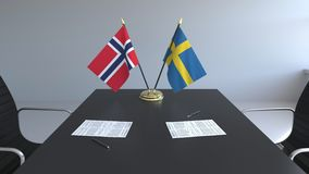 Banderas de Noruega y de Suecia y papeles en la tabla Negociaciones y firma de un acuerdo internacional 3D conceptual almacen de metraje de vídeo