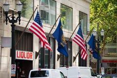 Banderas de Oregon y de los E.E.U.U. en el edificio fotos de archivo