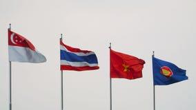 Banderas de países de Asia sudoriental que agitan en el cielo gris metrajes
