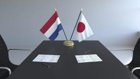 Banderas de Países Bajos y de Japón y papeles en la tabla Negociaciones y firma de un acuerdo internacional Conceptual metrajes