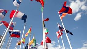 Banderas de países diferentes que agitan en cielo azul metrajes