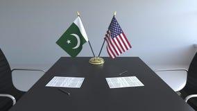 Banderas de Paquistán y de los Estados Unidos y papeles en la tabla Negociaciones y firma de un acuerdo internacional almacen de metraje de vídeo