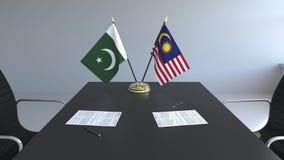 Banderas de Paquistán y de Malasia y papeles en la tabla Negociaciones y firma de un acuerdo internacional Conceptual metrajes