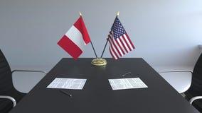 Banderas de Perú y de los Estados Unidos y papeles en la tabla Negociaciones y firma de un acuerdo internacional almacen de video