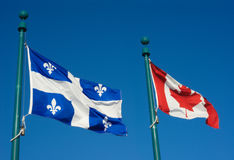 Banderas de Quebec y de Canadá que agitan en el viento junto en el cielo azul Fotografía de archivo