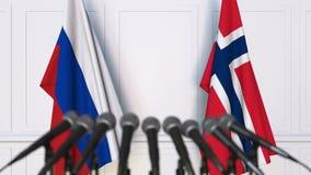 Banderas de Rusia y de Noruega en la rueda de prensa internacional de la reunión o de las negociaciones metrajes