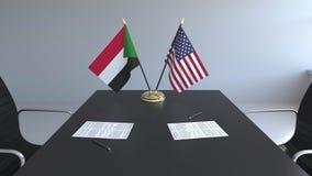 Banderas de Sudán y de los Estados Unidos y papeles en la tabla Negociaciones y firma de un acuerdo internacional almacen de video