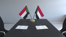 Banderas de Sudán y de los papeles en la tabla Negociaciones y firma de un acuerdo Animación conceptual 3D metrajes