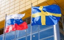 Banderas de Suecia y de Rusia que agitan contra la tienda de IKEA Imágenes de archivo libres de regalías