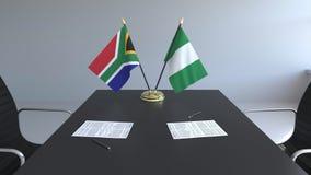 Banderas de Suráfrica y de Nigeria y papeles en la tabla Negociaciones y firma de un acuerdo internacional metrajes