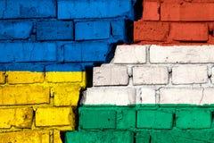 Banderas de Ucrania y de Hungría en la pared de ladrillo con la grieta grande en el centro S?mbolo de problemas entre los pa?ses imagenes de archivo