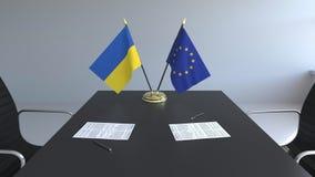 Banderas de Ucrania y la UE de la unión europea y los papeles en la tabla Negociaciones y firma de un acuerdo internacional metrajes