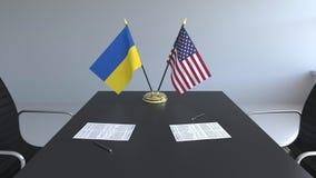 Banderas de Ucrania y de los Estados Unidos y papeles en la tabla Negociaciones y firma de un acuerdo internacional almacen de video