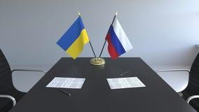 Banderas de Ucrania y de Rusia y papeles en la tabla Negociaciones y firma de un acuerdo internacional 3D conceptual metrajes
