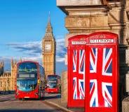 Banderas de unión británicas en cabinas de teléfono contra Big Ben en Londres, Inglaterra, Reino Unido Foto de archivo